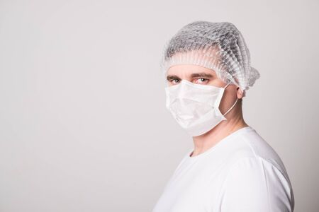 Doctor in a medical mask and hat. Man in a medical mask. Doctor man in a medical mask.