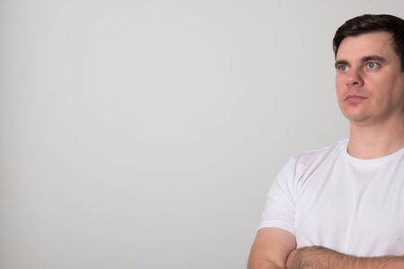 Positive young man. Pretty man in a white shirt. Фото со стока