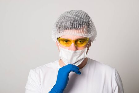 Doctor in a surgical mask, gloves and glasses. Surgeon before the operation. Young man in a medical mask.