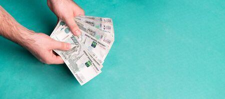 Man holds Russian money. Financial theme. Money in men's hands.