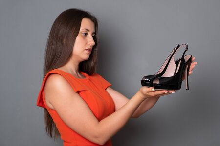Beautiful young woman holds high-heeled shoes. Brunette in black dress.