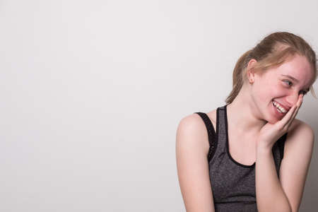 Teen girl in a sports top listens to music on headphones. Banner with blank space for text. Standard-Bild