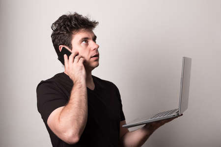 Man works on a laptop with a mobile phone. Happy man talking on a cell phone and laptop. Standard-Bild