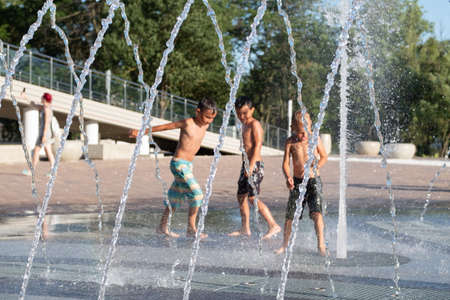 Kerch/Russia - June 27, 2020: Happy children laugh and splash in fountain in the summer park.