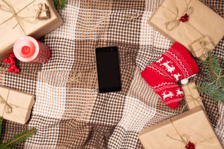 Christmas online shopping with phone. Online shopping concept - full Shopping Cart and gift box.screen of smartphone with copy space. Archivio Fotografico