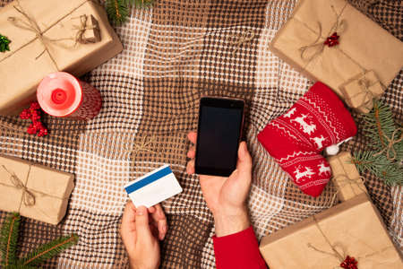 Christmas online shopping with phone. Online shopping concept, gift box. Man buyer makes order at screen of smartphone with copy space.