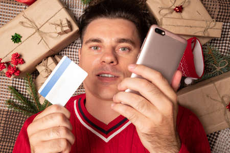 Christmas online shopping with phone. Online shopping concept - full Shopping Cart and gift box. Man buyer makes order at screen of smartphone with copy space.