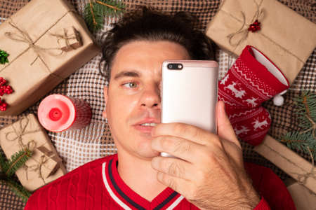 Christmas online shopping with phone. Online shopping concept. Man buyer makes order at screen of smartphone with copy space. Archivio Fotografico