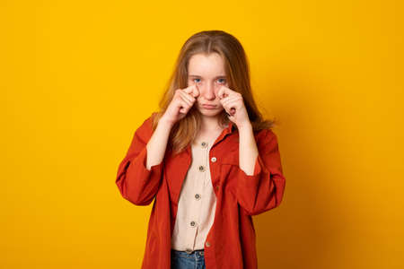 Depressed teen girl wipes tears cries from despair has displeased sad face expression wears neat clothes faces unsolvable problems in life. Personal difficulties.