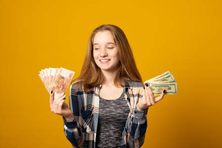 Cute young girl in casual clothes holds money, dollars in one hand and Russian rubles in the other on a yellow background.