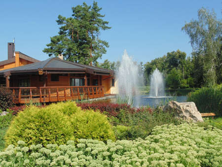 A country house with a fountain and a lake