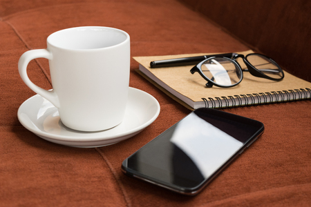 red sofa: Cup,cup of coffee and smartphone with diary note on red carpet or sofa background Stock Photo