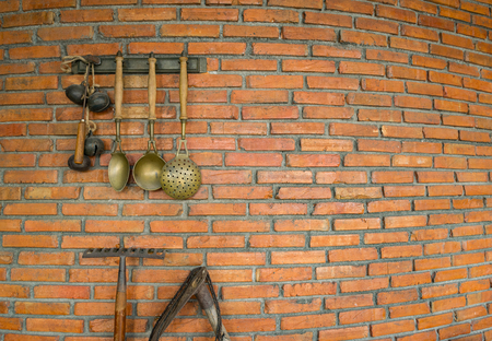 Brick wall with a spade and ladle hanging