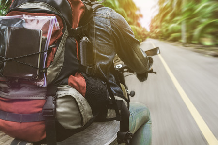 The man who driving motorcycle on the road for travel to somewhere