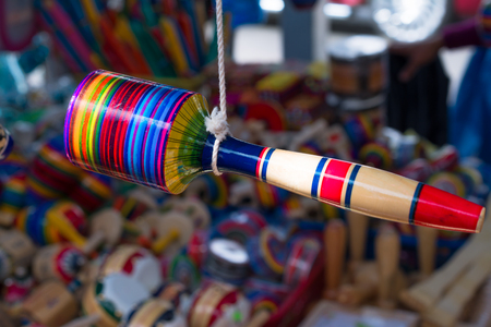 The maraca hangs from the thread.