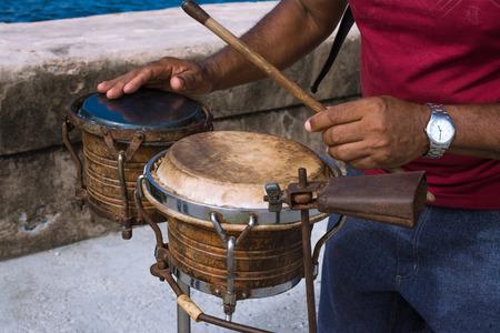 The musician plays the bongos on the boardwalk of Havana Cuba.