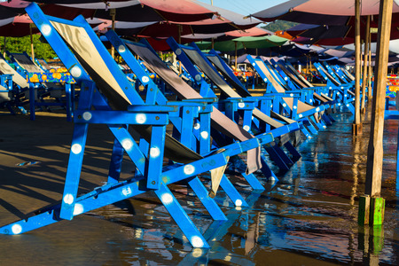 The blue chairs are getting wet by the waves on the beach. 版權商用圖片