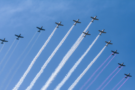 The twelve aerobatic plans are emitting green, white and red smoke.