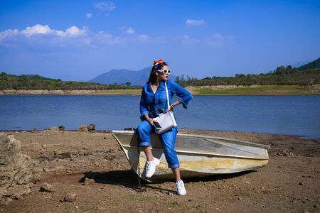 The young woman is sitting on the boat that is in the Corrinchis dam in Mascot Jalisco.