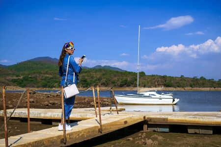 The young woman is walking towards the boat that is in the Corrinchis dam in Mascot Jalisco.
