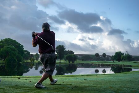 The player has hit the golf ball and the tee with great force. 写真素材