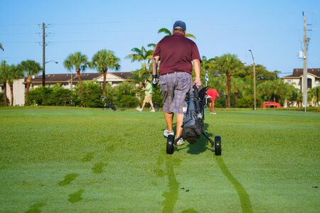 The golf player is heading towards the other hole where his playmates are.