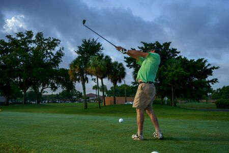 The golf player makes a very high movement of his arms.