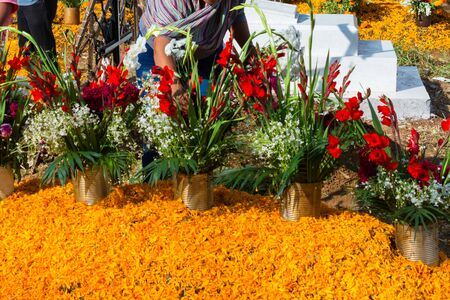 A lady has placed many orange and red flowers on her family's grave on the day of the dead. Foto de archivo