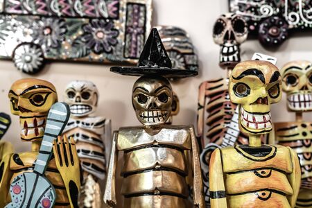 The skulls have different designs on their clothing and one has a black hat.
