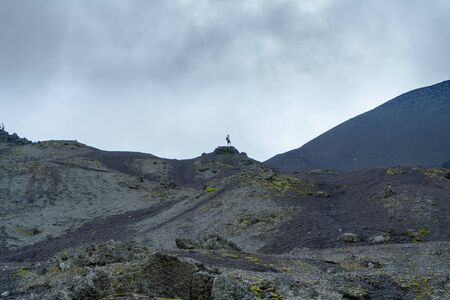 A young man from a very high rock contemplates the beauty of the Pacaya volcano in Guatemala. Banco de Imagens