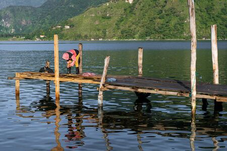 The boy is fishing and waits patiently on the dock of Lake Atitlan Guatemala.