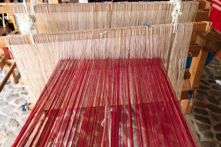 The standing loom has red and white cotton thread.