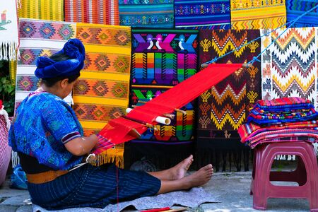 Maya woman is weaving with her waist loom on a street in San Antonio Palopo Guatemala.