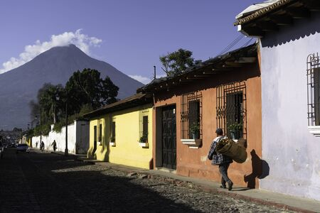 A man walks with his flowers on a street in Antigua Guatemala.