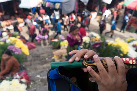 A young Maya is playing her flute at the Chichicastenango Guatemala market.