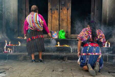Two women are praying on their knees in the cathedral of Santo Tomás Chichicastenango.