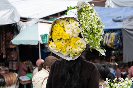 A Mayan woman is carrying on her head bouquets of flowers at the Chichicastenango market in Guatemala.