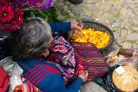 A woman is sitting on the stairs at the Chichicastenango market in Guatemala. Foto de archivo