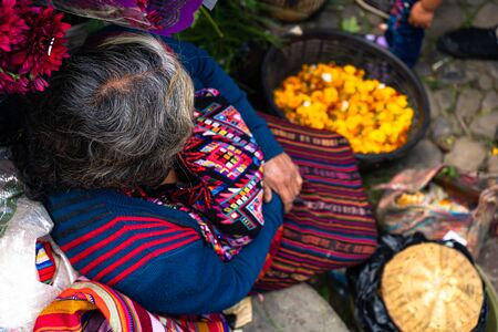 A Mayan woman is offering her flower petals in the market.