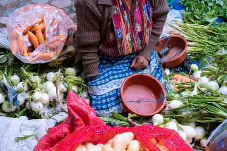 A Mayan woman is selling vegetables in the market.