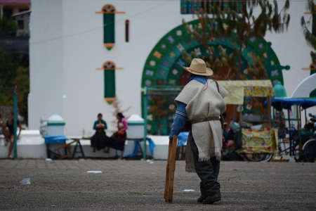 A man walks leaning on his cane in the plaza of San Juan Chamula Chiapas.