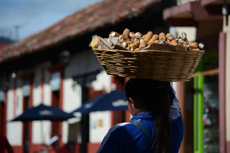 The young woman carries sweets in a basket on his head.