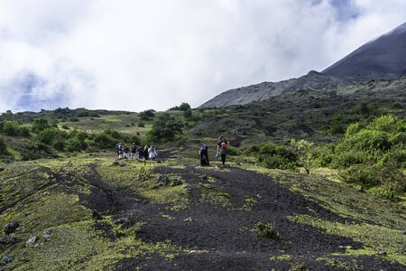 There are many young people who are climbing near the crater of the Pacaya volcano to see the lava.