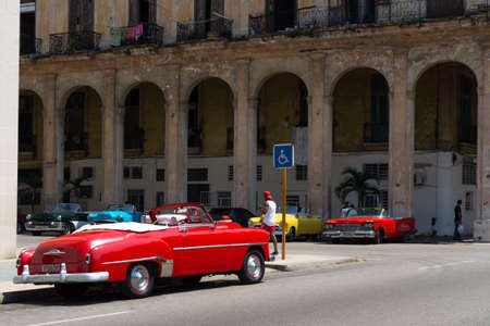 Havana, Cuba - August 25 2018: There are three classic taxis next to the Gran Hotel Manzana Kempiski in Old Havana.