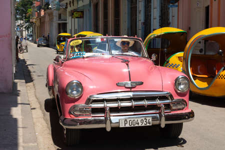Havana, Cuba - August 25 2018: Classic cars and a bicycle are in a central street of Old Havana. 新闻类图片