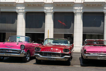 Havana, Cuba - August 25 2018: There are several people and classic cars that are circulating on a street in Old Havana.