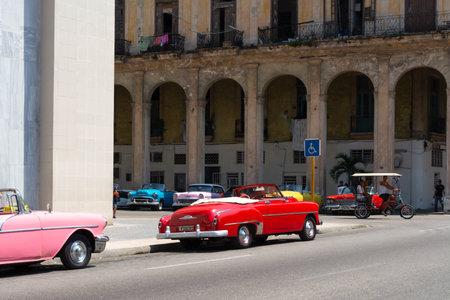Havana, Cuba - August 25 2018: A classic pink car is driving down a street in Old Havana.