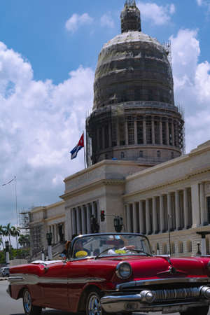 Havana, Cuba - August 25 2018: A red classic car is driving along Paseo Martí in front of the National Capitol of Cuba in Old Havana. 新闻类图片
