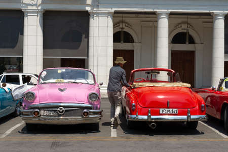 Havana, Cuba - August 25 2018: The driver is going to open the door of the classic taxi parked in Agramonte street next to the Gran Hotel Manzana Kempiski in Old Havana.