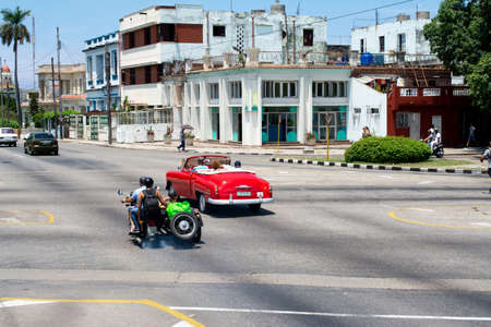 Havana, Cuba - August 25 2018: On an avenue in Havana there are several people traveling on a motorcycle made in Russia with their sidecar and a red classic car.